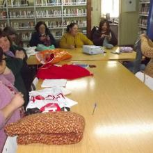 Women meeting in the library with their sewing and knitting.