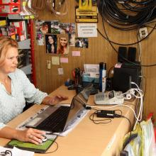 A successful jobseeker at her place of employment in an automobile sales outlet.