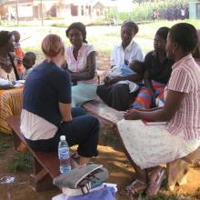 A health workers discussing health issues with a group of women.