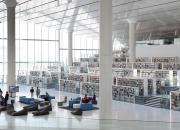 Inside the Qatar National Library, showing book shelves, seating and good light from floor to ceiling windows and skylights.
