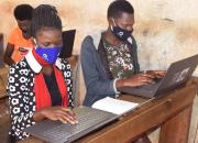 Two young women learning computer skills in a Ugandan public library.