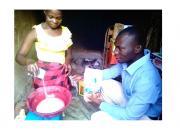 Zariakah Kyozira practising new baking skills at home, watched by Isa Maganda, Isa Maganda, Chief Librarian at Nambi Sseppuuya Community Resource Centre in Uganda.
