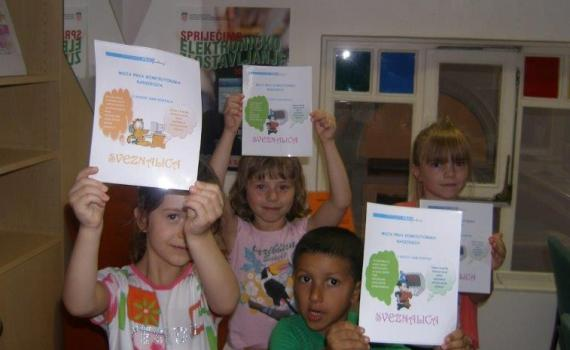Roma and non-Roma children show off certificates for achievements in ICT training.